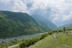 Ο δρόμος κατά τη θερινή άποψη Genaldon φαραγγιών και ποταμών Karmadon Βόρεια Οσετία, Ρωσία βουνά Καύκασου Στοκ Εικόνες