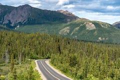 Ο δρόμος με πολλ'ες στροφές περνά από ένα βόρειο δάσος στο εθνικό πάρκο Αλάσκα Denali καλοκαίρι ημέρας ηλιόλουστο σκι βουνών εστί στοκ φωτογραφία