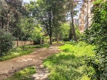 Ο δρόμος που μπαίνει στο προαύλιο του κατοικημένου κτηρίου, το ναυπηγείο με τα ανθίζοντας δέντρα και την αλκόβα Στοκ Εικόνες