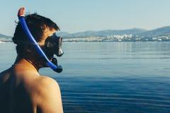 Ο δύτης νεαρών άνδρων με τη μάσκα σκαφάνδρων και κολυμπά με αναπνευτήρα στο υπόβαθρο της θάλασσας με το διάστημα r Στοκ Φωτογραφίες