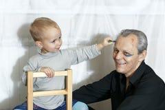 Ο εγγονός βάζει makeup στον παππού στοκ φωτογραφίες