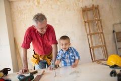 Ο εγγονός βοηθά τον παππού σε ένα εργαστήριο ξυλουργών ` s Στοκ Εικόνα