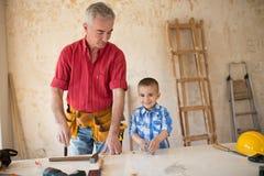 Ο εγγονός βοηθά τον παππού σε ένα εργαστήριο ξυλουργών ` s Στοκ Φωτογραφίες