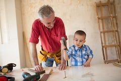 Ο εγγονός βοηθά τον παππού σε ένα εργαστήριο ξυλουργών ` s Στοκ εικόνες με δικαίωμα ελεύθερης χρήσης