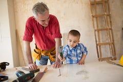 Ο εγγονός βοηθά τον παππού σε ένα εργαστήριο ξυλουργών ` s Στοκ Εικόνες
