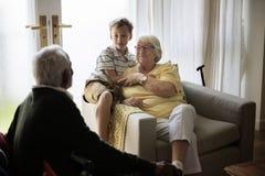 Ο εγγονός είναι σε ένα καθιστικό με τους παππούδες και γιαγιάδες Στοκ φωτογραφίες με δικαίωμα ελεύθερης χρήσης