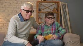 Ο εγγονός ταΐζει τον παππού του με τα τσιπ από το χέρι του Ο παππούς και ο εγγονός κάθονται στον καναπέ και την προσοχή απόθεμα βίντεο