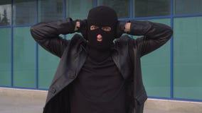 Ο εγκληματικός κλέφτης ή ο ληστής ατόμων στη μάσκα κρατά τα χέρια του πέρα από τα αυτιά του για να μην ακούσει απόθεμα βίντεο