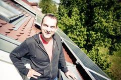 Ο εγχώριος ιδιοκτήτης είναι ευχαριστημένος από τα ηλιακά πλαίσια στη στέγη του στοκ εικόνες