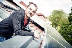 Ο εγχώριος ιδιοκτήτης είναι ευχαριστημένος από τα ηλιακά πλαίσια στη στέγη του Στοκ εικόνες με δικαίωμα ελεύθερης χρήσης