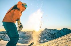 Ο ειδικός επαγγελματικός σκιέρ στο ηλιοβασίλεμα χαλαρώνει επάνω τη στιγμή στη γαλλική βουνοπλαγιά ορών στοκ εικόνα