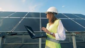 Ο ειδικός ηλιακής ενέργειας περπατά κατά μήκος μιας κατασκευής μπαταριών με το lap-top της απόθεμα βίντεο