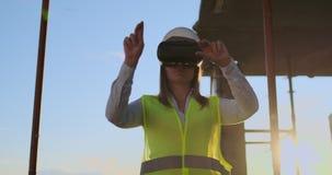 Ο ειδικός οικοδόμος μηχανικών γυναικών στα γυαλιά και το κράνος VR ελέγχει την πρόοδο της κατασκευής ουρανοξυστών που κινεί τα χέ απόθεμα βίντεο