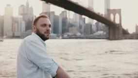 Ο ειρηνικός καυκάσιος νεαρός άνδρας εμφανίζεται και στέκεται στο ανάχωμα ποταμών κοντά στο τοπίο πόλεων της Νέας Υόρκης, απολαμβά απόθεμα βίντεο