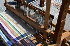 Ο λειτουργικός ιστορικός ξύλινος χέρι-αργαλειός που υφαίνει το ζωηρόχρωμο χαλί με τις κάθετες γραμμές επέδειξε στο φεστιβάλ μεσαι στοκ φωτογραφία με δικαίωμα ελεύθερης χρήσης
