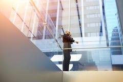Ο ειδικευμένος αρσενικός δικηγόρος μιλά με τον πελάτη μέσω του τηλεφώνου κυττάρων κατά τη διάρκεια του σπασίματος εργασίας στην α Στοκ φωτογραφία με δικαίωμα ελεύθερης χρήσης