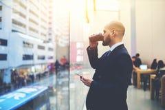 Ο ειδικευμένος επιχειρηματίας προσέχει στο παράθυρο και σκέφτεται για τη μελλοντική συνεδρίασή του Στοκ εικόνα με δικαίωμα ελεύθερης χρήσης