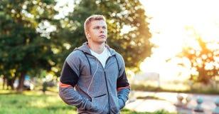 Ο εκπαιδευτής αθλητών στα ακουστικά ακούει ένα audiobook, βέβαιο βλέμμα Ο θερινός τρόπος ζωής, κίνητρο είναι ισχυρός υπαίθρια Στοκ Φωτογραφία