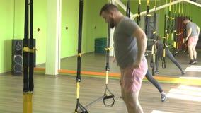 Ο εκπαιδευτής διδάσκει στη γυμναστική για να ασκηθεί ένα άτομο στις αρθρώσεις του TRX εκτελώντας μια του προσώπου ώθηση άσκησης απόθεμα βίντεο