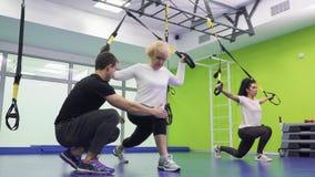 Ο εκπαιδευτής διδάσκει την ηλικιωμένη γυναίκα για να καθίσει οκλαδόν σωστά με τις ζώνες φιλμ μικρού μήκους