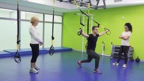 Ο εκπαιδευτής παρουσιάζει στις γυναίκες πόσο σωστά στάσεις οκλαδόν χρησιμοποιώντας τις ζώνες στη γυμναστική απόθεμα βίντεο
