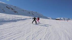 Ο εκπαιδευτικός διδάσκει το σπουδαστή στο σκι Alpen στο θέρετρο βουνών το χειμώνα απόθεμα βίντεο