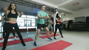 Ο εκπαιδευτικός ικανότητας συνεργάζεται με την ομάδα νέων γυναικών στη γυμναστική ικανότητας φιλμ μικρού μήκους