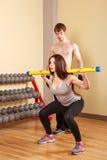 Ο εκπαιδευτής εξηγεί την άσκηση με τα κορίτσια fitbar Στοκ Φωτογραφίες