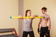 Ο εκπαιδευτής εξηγεί την άσκηση με τα κορίτσια fitbar Στοκ φωτογραφία με δικαίωμα ελεύθερης χρήσης