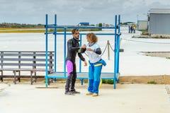 Ο εκπαιδευτικός ελεύθερων πτώσεων με αλεξίπτωτο της διδάσκει τη σωστή θέση ελεύθερων πτώσεων με αλεξίπτωτο πρίν πηδά Στοκ Φωτογραφία