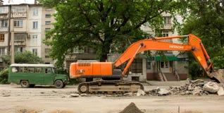 Ο εκσκαφέας ανασκάπτει την άσφαλτο Στοκ εικόνες με δικαίωμα ελεύθερης χρήσης