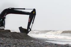 Ο εκσκαφέας λειτουργεί με ένα σύνολο κάδων των πετρών στην ακτή στο θυελλώδη καιρό Στοκ Εικόνες