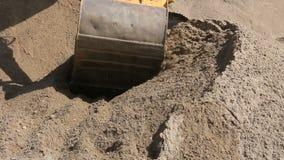 Ο εκσκαφέας προετοιμάζει το σωρό της άμμου για τη φόρτωση στο φορτηγό στο εργοτάξιο φιλμ μικρού μήκους