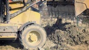 Ο εκσκαφέας σκάβει τα θεμέλια του σπιτιού Ανασκαφή της τρύπας Μηχανήματα κατασκευής, αλεσμένες εργασίες Digger εργασίες για την ο απόθεμα βίντεο