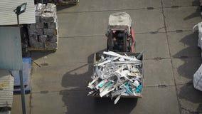 Ο εκσκαφέας φέρνει το μέταλλο και άλλα συντρίμμια κατά μήκος ενός δρόμου ασφάλτου για την ανακύκλωσή του και την ταξινόμηση για τ απόθεμα βίντεο