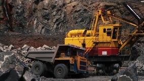 Ο εκσκαφέας φορτώνει μια πέτρα στο βαρύ φορτηγό στο γρανίτη μεταλλείας λατομείων φιλμ μικρού μήκους
