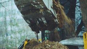 Ο εκσκαφέας χύνει τη γη από τον κάδο απόθεμα βίντεο