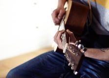 Ο εκτελεστής παίζει μια ξύλινη ακουστική κιθάρα στοκ εικόνες