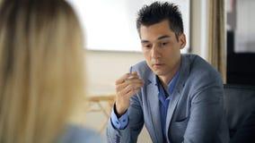 Ο εκτελεστικός διευθυντής μιλά με την ξανθή γυναίκα για τη μίσθωση φιλμ μικρού μήκους