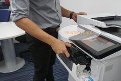 Ο εκτυπωτής γραφείων τρέχει από το μελάνι και την απαραίτητη κασέτα τονωτικού που τίθενται από τον επιχειρηματία στοκ φωτογραφίες