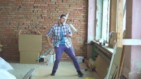 Ο εκφραστικός χαρούμενος αρσενικός οικοδόμος τραγουδά και χορεύει εργαζόμενος απόθεμα βίντεο
