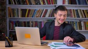 Ο ελκυστικός άνδρας σπουδαστής που εργάζεται να πάρει lap-top από το μήνυμα στο τηλέφωνο που είναι ευτυχές και που γελά μέσα απόθεμα βίντεο