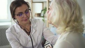 Ο ελκυστικός ανώτερος ασθενής κάθεται χωρίς οποιαδήποτε κίνηση και ενημερώνει βαθειά απόθεμα βίντεο