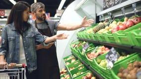 Ο ελκυστικός ενδιαφερόμενος γυναίκα πελάτης μιλά στην όμορφη εργασία πωλητών τύπων φιλική στο τμήμα φρούτων μέσα φιλμ μικρού μήκους