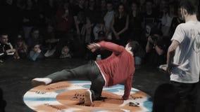 Ο ελκυστικός ενεργός τύπος brunette σκούρο κόκκινο σε hoody αποδίδει δυναμικά στη σκηνή απόθεμα βίντεο