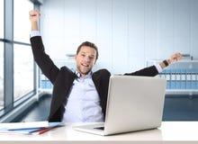 Ο ελκυστικός επιχειρηματίας ευτυχής και ταραχώδης στη συνεδρίαση εργασίας γραφείων στο γραφείο υπολογιστών ικανοποίησε τον εορτασ Στοκ Εικόνες