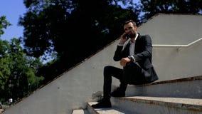 Ο ελκυστικός επιχειρηματίας νεαρών άνδρων με μια συνεδρίαση γενειάδων σε ένα πάρκο σε μια συγκεκριμένη σκάλα και την ομιλία στο τ απόθεμα βίντεο
