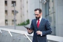 Ο ελκυστικός επιχειρηματίας στο κοστούμι και ο κόκκινος δεσμός ελέγχουν ή διαβάζουν στην ψηφιακή ταμπλέτα το υπαίθριο κτίριο γραφ στοκ φωτογραφίες