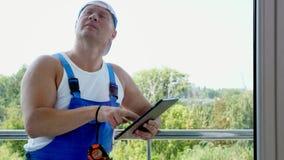 Ο ελκυστικός εργάτης οικοδομών κάνει τις σημειώσεις στην ταμπλέτα Άτομο υπηρεσιών που εγκαθιστά το παράθυρο απόθεμα βίντεο
