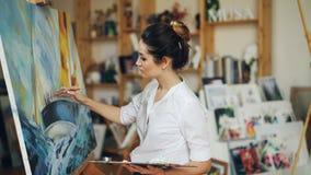 Ο ελκυστικός ζωγράφος γυναικών χρωματίζει το σκάφος και τη θάλασσα στην εικόνα που δημιουργεί όμορφο seascape χρησιμοποιώντας τα  απόθεμα βίντεο